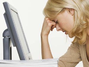 Exhausted and frustrated woman at a computer