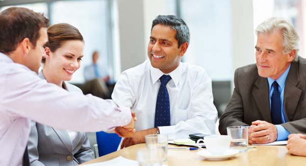 Four business people in a meeting, two shaking hands
