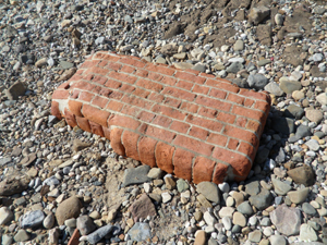 Part of a brick wall lying on a beach